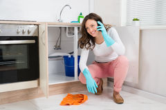 Woman Wiping While Talking On Mobile Phone Stock Photo