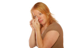 Woman wiping a tear. Woman on an isolated background wiping away a tear Stock Photos