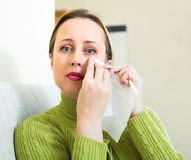 Woman wiping tears with paper towel Royalty Free Stock Image
