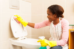 Woman wiping toilet seat Royalty Free Stock Photo