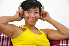 Woman with wireless headphone listens to music. Beautiful woman wearing yellow top listens to music with wireless headphone Stock Photography
