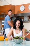 Woman wirh salad in the kitchen and man washing Royalty Free Stock Photos