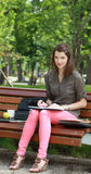 Woman Wiritng Outside in a Park. Portrait of a young woman writing in a notebook outside in a park Royalty Free Stock Image