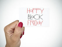 Woman wishing a happy black friday. Woman with her nails painted red showing a signboard with the text happy black friday written in it royalty free stock photo