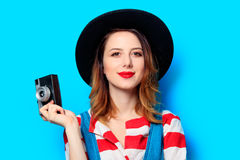 Woman wit camera on blue background. Portrait of young smiling red-haired white european woman in hat and red striped shirt with camera on blue background Royalty Free Stock Images