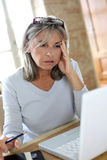 Woman wit grey hair working with a worried look Royalty Free Stock Images