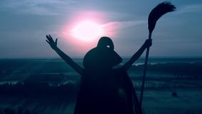 Woman in a witch costume and broom posing cityscape at night. Sorceress in hat and cloak holding besom raising hands on the field view on evening blue sky stock video footage