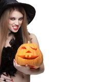 Woman in witch costume opens carved Halloween pumpkin stock photo