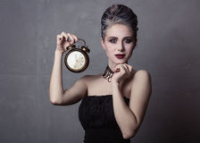 Woman in witch halloween costume. Portrait of young woman in witch halloween costume with alarm clock, smiling over grey background Royalty Free Stock Images