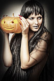 Woman witch holding pumpkin Royalty Free Stock Images