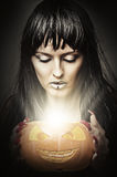 Woman witch holding pumpkin Stock Image