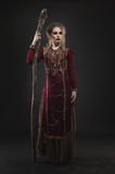 Woman witch with magic pikestaff. In studio Stock Photography