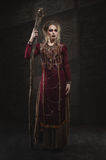 Woman witch in red dress. And magic pikestaff Royalty Free Stock Photos