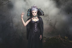 Woman witch smoke. Beautiful woman conjures witch in the woods around the smoke stock photo