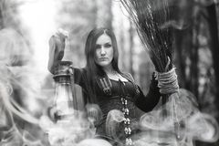 Woman in a witch suit in a dense forest. A woman in a witch suit in a dense forest on a ritual Royalty Free Stock Photography