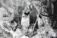 Woman in a witch suit in a dense forest. A woman in a witch suit in a dense forest on a ritual Royalty Free Stock Image