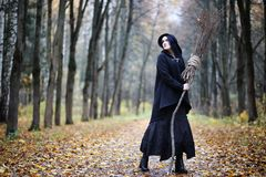 A woman in a witch suit in a forest. A woman in a witch suit in a dense forest on a ritual royalty free stock photo
