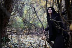 A woman in a witch suit in a forest. A woman in a witch suit in a dense forest on a ritual stock photos