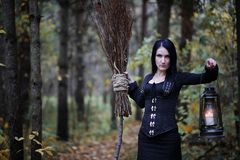 A woman in a witch suit in a forest. A woman in a witch suit in a dense forest on a ritual stock photography