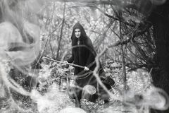Woman in a witch suit in a dense forest. A woman in a witch suit in a dense forest on a ritual Royalty Free Stock Photos