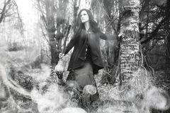 Woman in a witch suit in a dense forest. A woman in a witch suit in a dense forest on a ritual Stock Photo