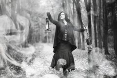 Woman in a witch suit in a dense forest. A woman in a witch suit in a dense forest on a ritual Royalty Free Stock Images