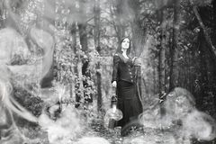 Woman in a witch suit in a dense forest. A woman in a witch suit in a dense forest on a ritual stock photography
