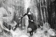 Woman in a witch suit in a dense forest. A woman in a witch suit in a dense forest on a ritual stock images