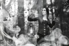 Woman in a witch suit in a dense forest. A woman in a witch suit in a dense forest on a ritual stock photos
