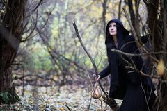 A woman in a witch suit in a forest Stock Photo