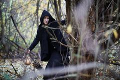 A woman in a witch suit in a forest Stock Image