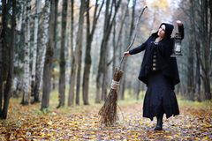 A woman in a witch suit in a forest. A woman in a witch suit in a dense forest on a ritual royalty free stock photography