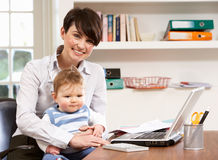 Woman With Baby Working From Home Using Laptop Stock Photography