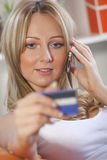 Woman With Credit Card And Cell Phone Royalty Free Stock Photography