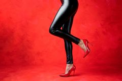 Woman With Sexy Legs Wearing Black Leggings And Red High Heel Shoes Stock Photos