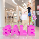 Woman With Shopping Bags Poses At Store Stock Image