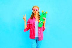 Free Woman With Skateboard Listens To Music In Wireless Headphones In A Pink Denim Jacket Royalty Free Stock Image - 111912966
