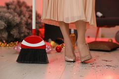 Free Woman With Sweep Broom Cleaning Messy Room After New Year Party, Closeup Stock Photo - 164386520