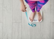 Woman With Tape Measuring Her Weight Using Scales Stock Images