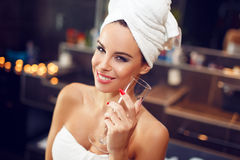 Free Woman With Towel Holding Glass Of Champagne In Bathroom Stock Photography - 65073352