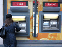 Cash from atm. Woman withdrawing cash from an atm banking machine of Societe Generale in Paris, France stock images