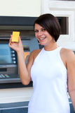 Woman withdrawing money from credit card at ATM Stock Photos