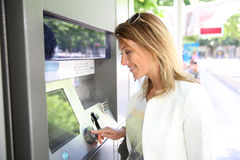 Woman withdrawing money from distributor Stock Photos