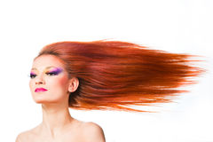 Woman withlong red hair fluttering on wind. Beautiful woman with multicolored make-up and long red hair fluttering on wind royalty free stock photo