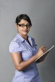 Woman witing with a pen on clipboard Stock Photos