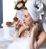 Woman witn soft big towel in the motning take breakfast in hotel spa lying in bath tub drinking glass of champagne Royalty Free Stock Image