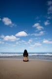 Woman Sitting on Sandy Beach Looking towards Horiz Royalty Free Stock Photo