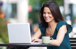 Woman wokring on her laptop at a sidewalk cafe Royalty Free Stock Image