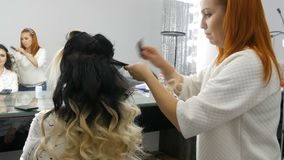 Woman Woman hairdresser stylist does a curl of curls of hair in a beauty salon with special curling iron. Long beautiful. Woman hairdresser stylist does a curl stock footage