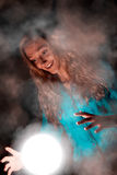 Woman in wonder. Young beautiful woman with long golden hair, dressed in blue clothes making some magic. She is looking happy to the light sphere between her royalty free stock photo
